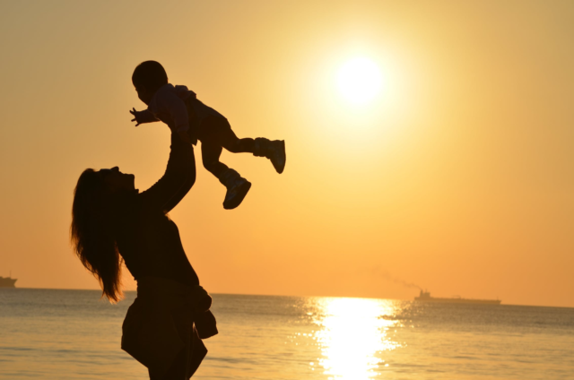 A sunset over the ocean casts a silhouette around a mother lifting her child above her head.