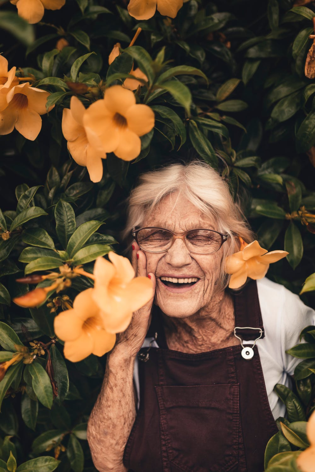 A grey-haired woman smiling widely, standing amid vines with yellow flowers.
