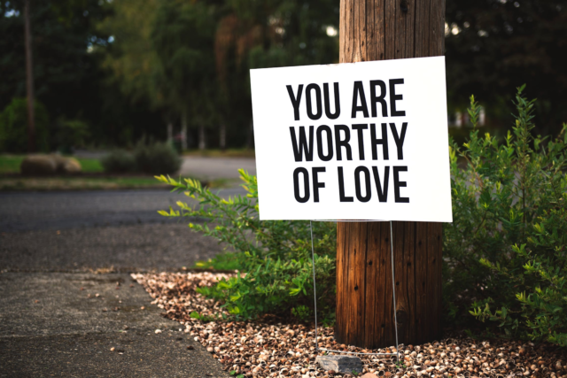 """A white sign with black text reading """"You are worthy of love"""" stands next to a wooden pole off a forest trail."""